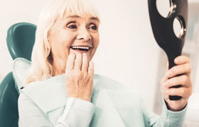 Smiling woman admires her new dental implants in DeLand