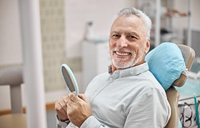 Older man with dental implants in DeLand smiling and holding mirror