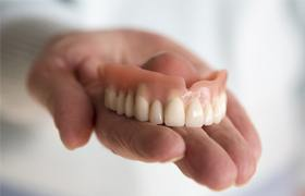 Someone holding an upper denture in their hand