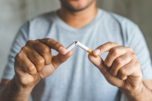 person breaking a cigarette in half to reduce their oral cancer risk