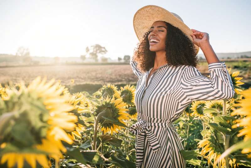 woman smiling in sunflower field during summer